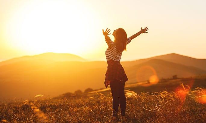 girl with background of mountains joyful