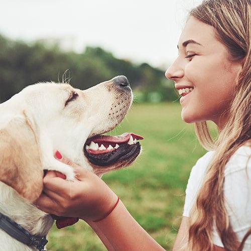 dog owner smiling at her dog