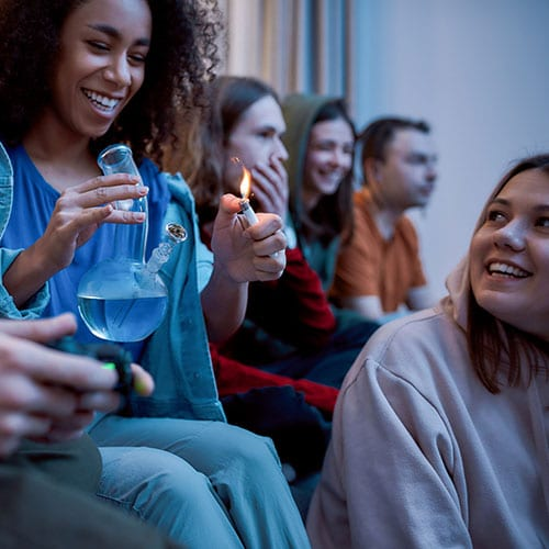 Teenagers Smoking In a Room From A Bong